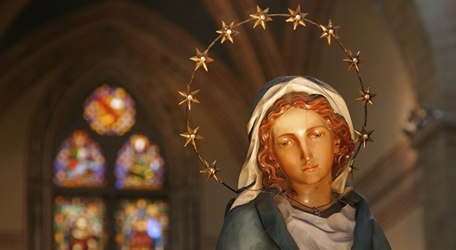 Colorful wooden statue of Mary in the Church of Santa Croce in Florence, Italy.